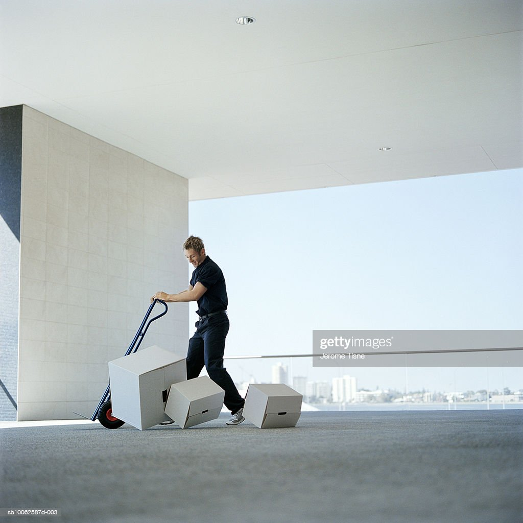 Delivery man dropping boxes from sack barrow outdoors : Stock Photo