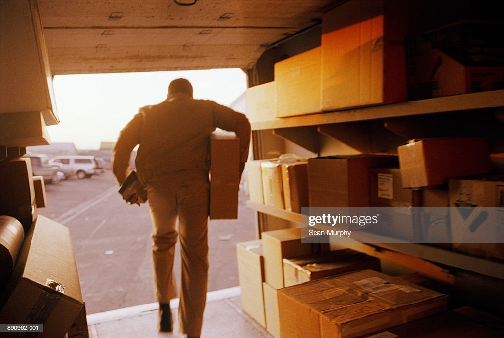 Delivery man exiting truck with package, rear view : Stock Photo