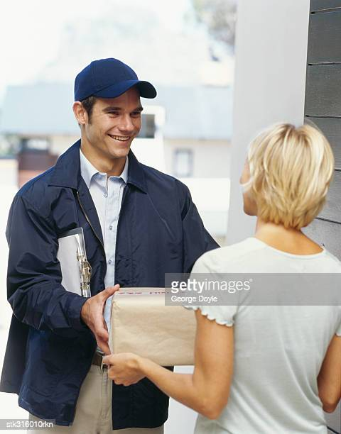 delivery man handing a parcel to a young woman