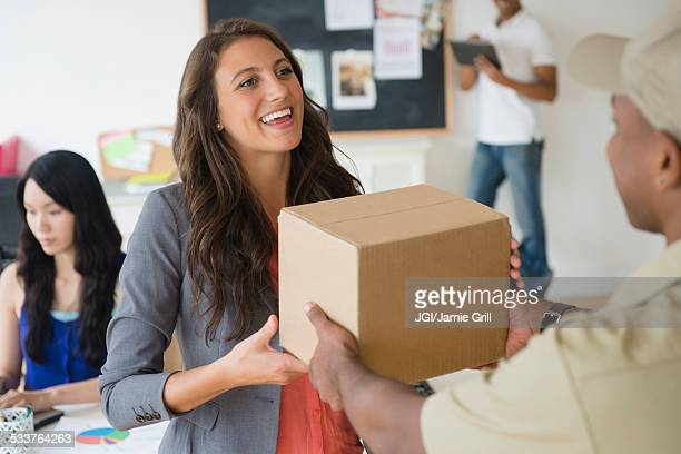 Delivery man handing cardboard box to businesswoman in office