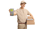 Delivery man holding a payment terminal and packages isolated on white background