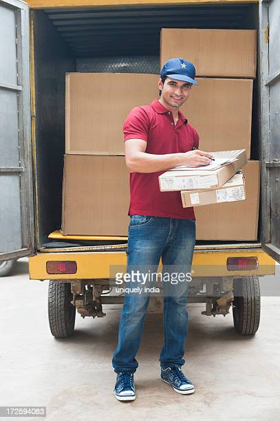 Delivery man holding cardboard boxes and smiling