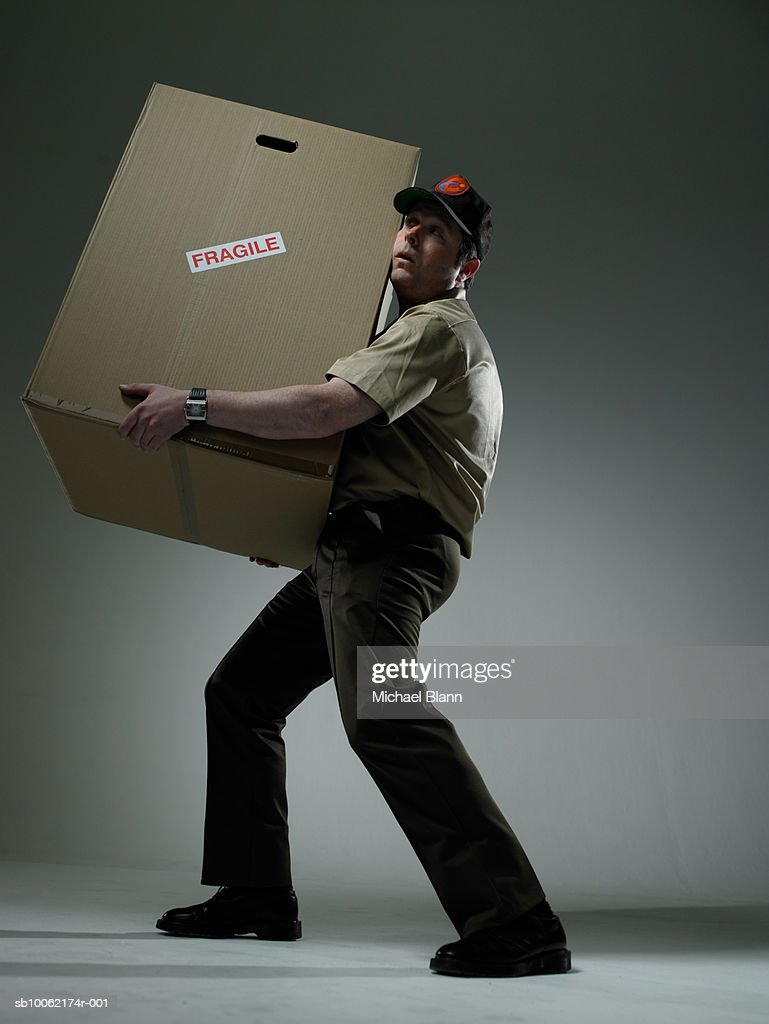 Delivery man holding large box : Stock Photo