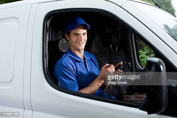 Delivery man in van with handheld computer