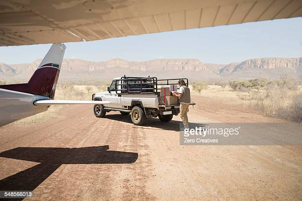 Delivery man loading parcels from airplane to truck, Wellington, Western Cape, South Africa