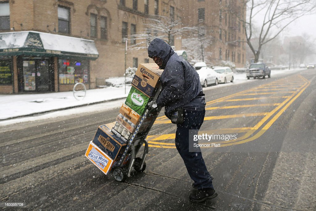 A delivery man navigates the streets in the snow on March 8, 2013 in the Brooklyn borough of New York City. As a week-old storm slowly moves out to sea, the New York City area is expecting 1 to 3 inches of snow with more in areas north and west of the city. The storm has caused flight delays at area airports and numerous schools have delayed start times.