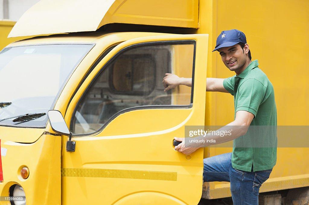 Delivery man opening the door of a van : Stock Photo