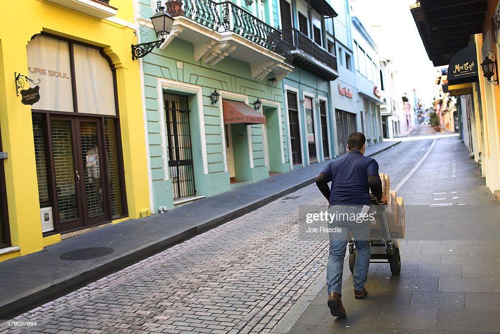 A delivery man pushes a cart through the streets a day after the Puerto Rican Governor Alejandro Garcia Padilla gave a televised speech regarding the...