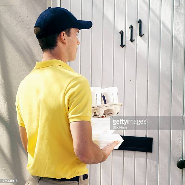 Delivery man standing outside door, holding stack of boxes, rear view