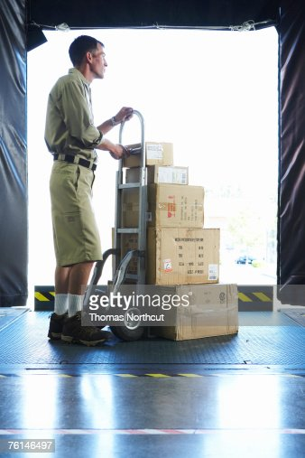 delivery man standing with boxes in loading bay side view stock foto getty images. Black Bedroom Furniture Sets. Home Design Ideas