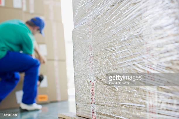 Delivery man taping cardboard boxes in warehouse
