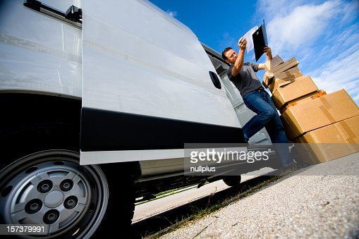 Delivery man unloading boxes from truck