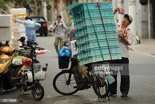 A delivery man unloads his bicycle on a street in Shanghai on September 26 2012 Japanese Prime Minister Yoshihiko Noda warned China in an interview...