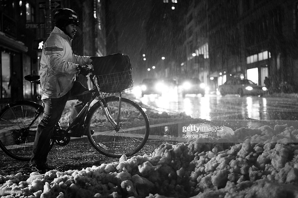 A delivery man waits for the light in the snow and rain on February 13, 2014 in New York City. In what is turning out to be one of the snowiest winter's in recent memory for New York City and much of the East Coast, Thursday's weather is expected to bring a wintery mix of sleet and snow with a total accumulation of over 8 inches of snow before ending early Friday morning.