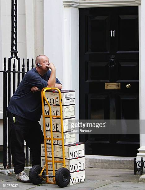 A delivery man waits to deliver cases of champagne to the residence of Britain's Chancellor of the Exchequer Gordon Brown during a cabinet meeting at...
