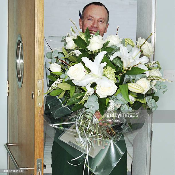 Delivery man with bouquet of flowers, smiling, portrait
