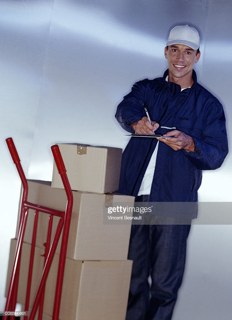 Delivery man with clipboard beside trolley of packages, portrait : Stock Photo