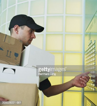 Delivery man with parcels by lift pressing button : Stock Photo