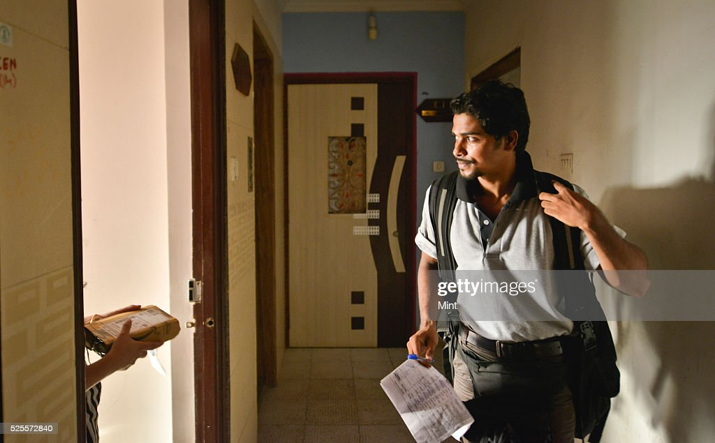 Delivery man, working for Amazon, delivers a package to a customer in an apartment complex on May 6, 2015 in Mumbai, India.