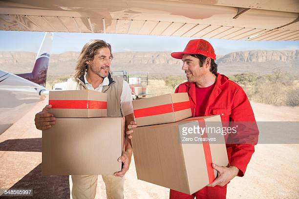 Delivery men carrying parcels off airplane