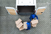 Directly above shot of delivery men unloading cardboard boxes from truck on street