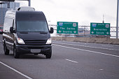The compact black mini van for the transport of commercial goods and parcels, as well as for use in a small business, traveling on the wide interstate multi-lines highway with traffic signs.