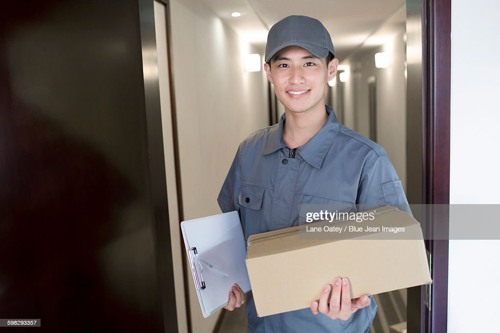 Delivery person holding package : Photo
