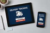 Delivery tracking concept on tablet and smartphone screen over gray table. All screen content is designed by me. Flat lay