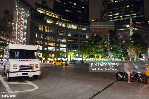 Delivery trucks a man on a small motorcycle and other vehicle traffic passes through Columbus Circle at night in Manhattan New York City New York...