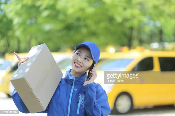 delivery woman carrying package while answering mobile phone