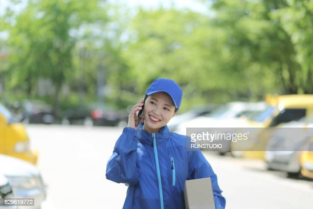 Delivery woman talking on cell phone with package