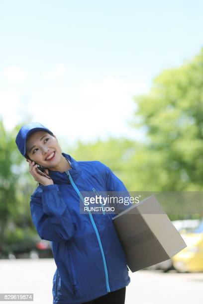 Delivery woman with package talking on cell phone