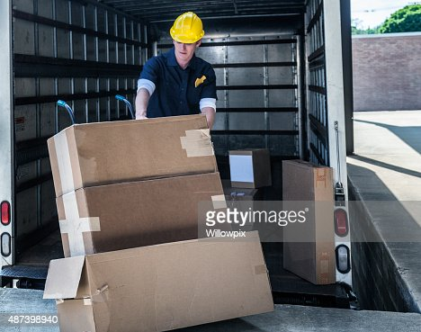 Delivery Worker Loading Damaged Boxes On Hand Truck