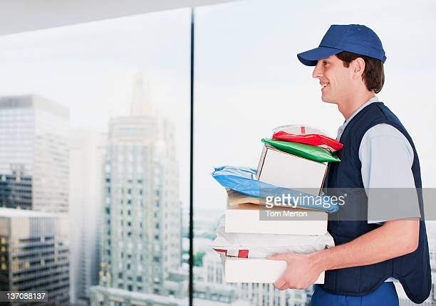Deliveryman carrying stack of packages