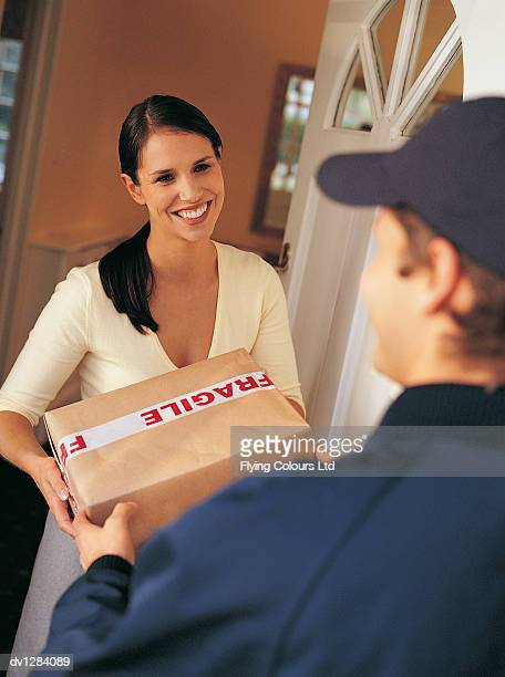 Deliveryman Handing Over a Parcel to a Smiling, Young Woman Standing at the Front Door of Her House