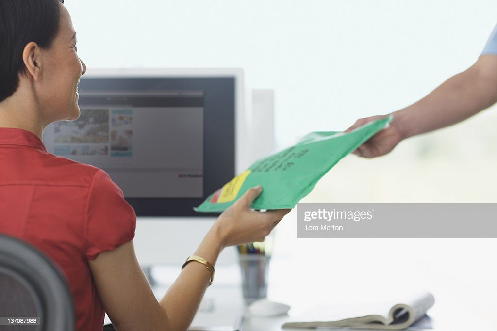 Deliveryman handing package to businesswoman : Stock Photo