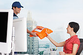 Deliveryman handing package to businesswoman