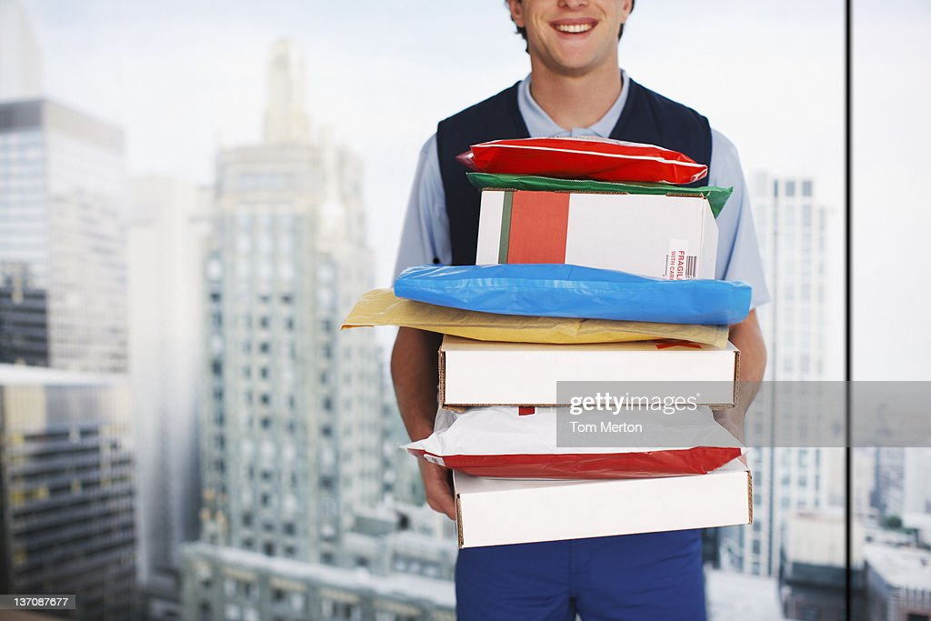 Deliveryman holding stack of packages : Stock Photo
