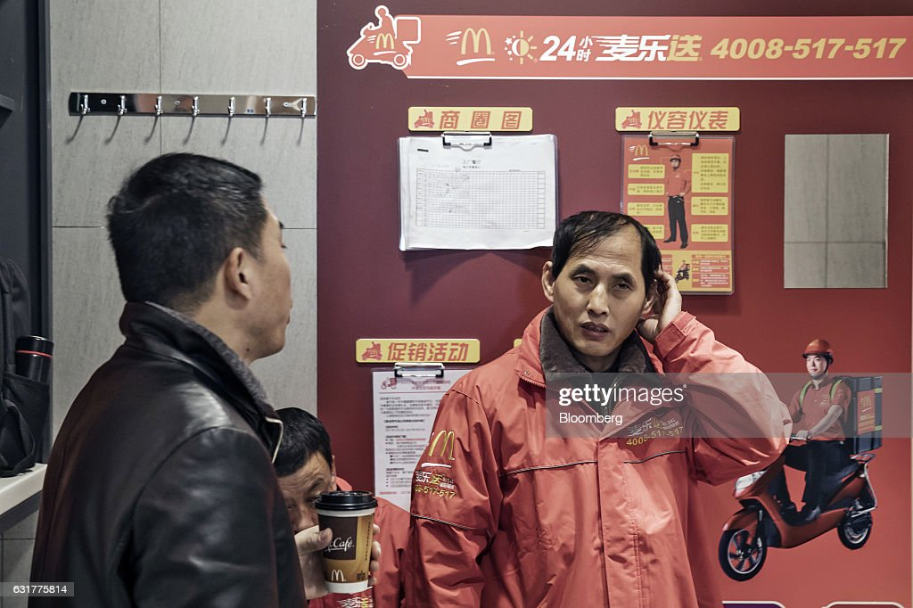 Deliverymen take a break inside a booth inside a McDonald's Corp. restaurant in Shanghai, China, on Friday, Jan. 13, 2017. McDonald's agreed to sell a controlling stake in its China and Hong Kong operations to a group of investors for about $1.7 billion, a key component of the fast-food giants reorganization in a market where its striving to catch up with more nimble rivals. Photographer: Qilai Shen/Bloomberg via Getty Images