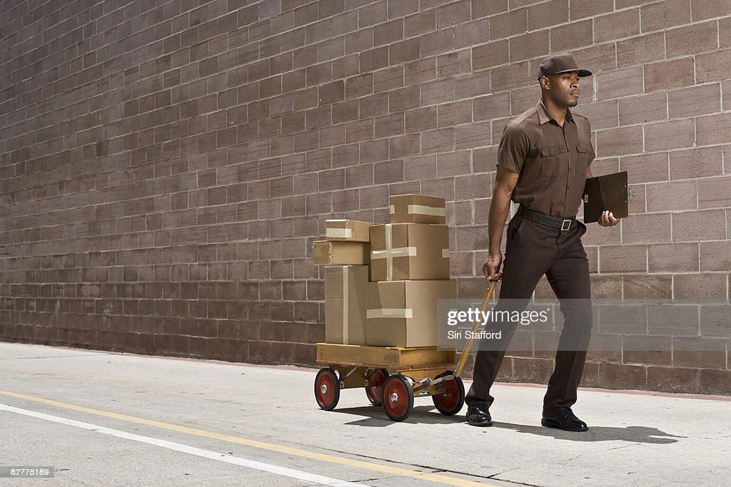 delivery-person carrying boxes on toy wagon : Foto stock