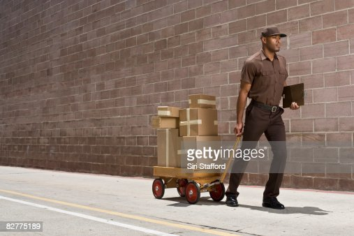 delivery-person carrying boxes on toy wagon : Stock Photo