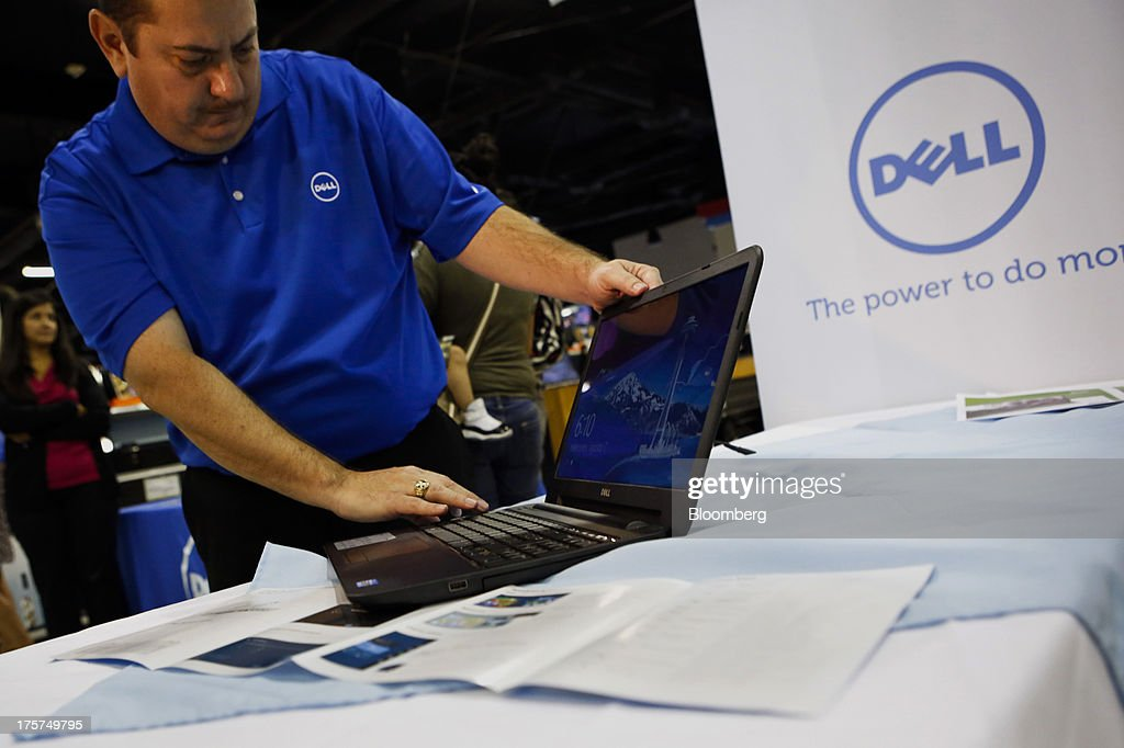 Dell Inc. employee Rad Moreno demonstrates features on an Inspiron 15 laptop during an event at a Curacao Department store in Los Angeles, California, U.S., on Wednesday, August 7, 2013. The Inspiron 15, an affordable notebook with an impressive battery life, is the only Spanish-language laptop manufactured and sold in the U.S. offered by Dell. Photographer: Patrick T. Fallon/Bloomberg via Getty Images