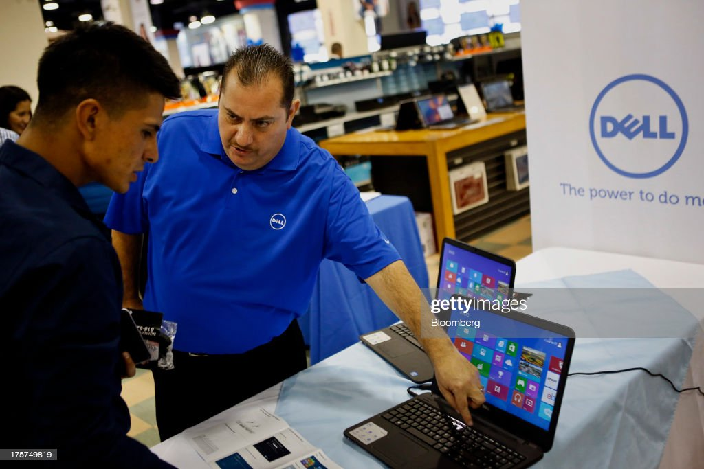 Dell Inc. employee Rad Moreno, right, demonstrates features on an Inspiron 15 laptop during an event at a Curacao Department store in Los Angeles, California, U.S., on Wednesday, August 7, 2013. The Inspiron 15, an affordable notebook with an impressive battery life, is the only Spanish-language laptop manufactured and sold in the U.S. offered by Dell. Photographer: Patrick T. Fallon/Bloomberg via Getty Images
