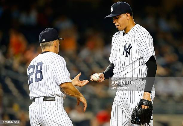 Dellin Betances of the New York Yankees hands the ball to manager Joe Girardi as he leaves a game against the Oakland Athletics in the tenth inning...