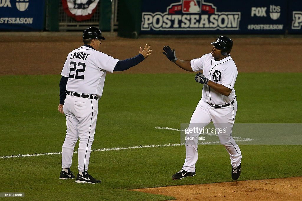 Delmon Young #21 of the Detroit Tigers greets third base coach Gene Lamont as Young scores on his solo home run in the bottom of the fourth inning against the New York Yankees during game three of the American League Championship Series at Comerica Park on October 16, 2012 in Detroit, Michigan.