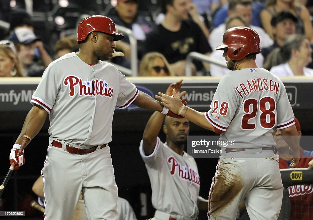 Delmon Young #3 of the Philadelphia Phillies congratulates teammate Kevin Frandsen #28 on scoring the tying run against the Minnesota Twins during the eighth inning of the game on June 11, 2013 at Target Field in Minneapolis, Minnesota. The Twins defeated the Phillies 3-2.