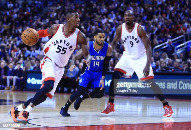 Delon Wright of the Toronto Raptors dribbles the ball as DJ Augustin of the Orlando Magic and Serge Ibaka look on during the second half of an NBA...