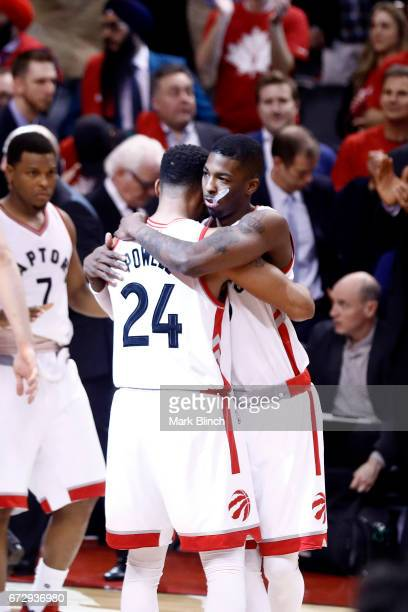 Delon Wright of the Toronto Raptors hugs teammate Norman Powell after defeating the Milwaukee Bucks during Game Five of the Eastern Conference...