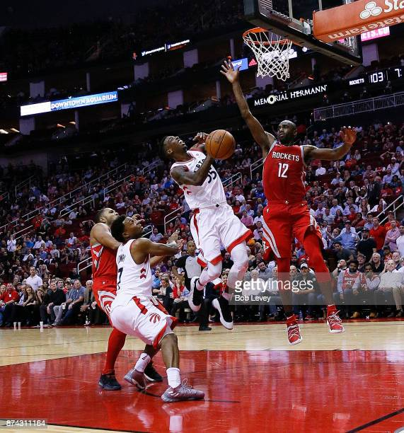 Delon Wright of the Toronto Raptors is fouled by Eric Gordon of the Houston Rockets as he drives to the basket as Kyle Lowry looks on and Luc Mbah a...