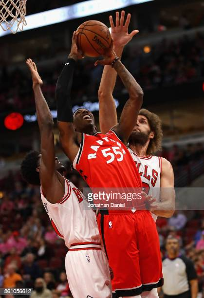 Delon Wright of the Toronto Raptors puts up a shot between Justin Holiday and Robin Lopez of the Chicago Bulls during a preseason game at the United...